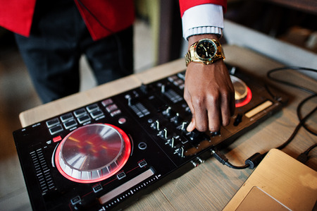 Hands of fashion african american man model DJ at red suit with dj controller. 免版税图像