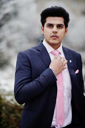 Elegant indian macho man model on suit and pink tie posed on winter day. 免版税图像