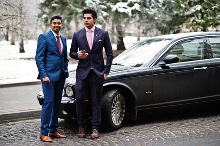 Two elegant indian fashionable mans model on suit posed at winter day against black classic car.