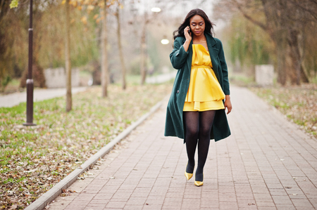 Stylish african american woman at green coat and yellow dress posed against autumn park and speaking on phone. 免版税图像