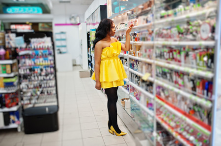 Stylish african american woman at yellow dreess posed at cosmetic store, buying make up accessories on beauty shop.
