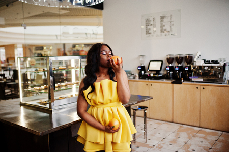 Stylish african american woman at yellow dreess posed at coffee house with two grapefruits on hands.