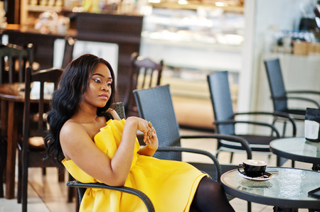 Stylish african american woman at yellow dreess posed at cafe with cup of cappuccino. Stock Photo