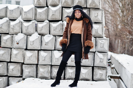 African american woman in sheepskin coat and cap posed at winter day against snowy stone background. Stockfoto