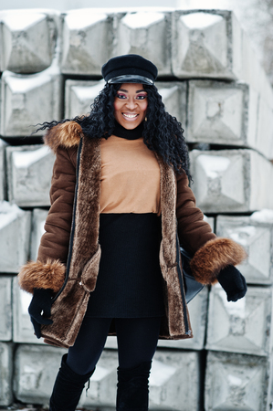 African american woman in sheepskin coat and cap posed at winter day against snowy stone background. Stock Photo