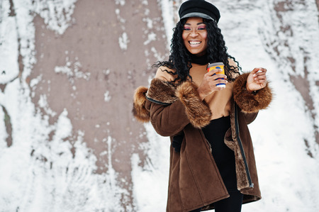 African american woman in sheepskin coat and cap posed at winter day against snowy background with cup of coffee. Stock Photo