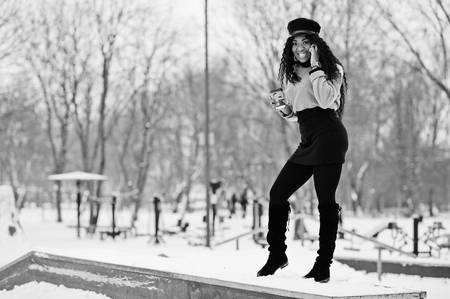 African american woman in black skirt, brown sweater and cap posed at winter day against snowy background, holding cup of coffee and speaking on phone.