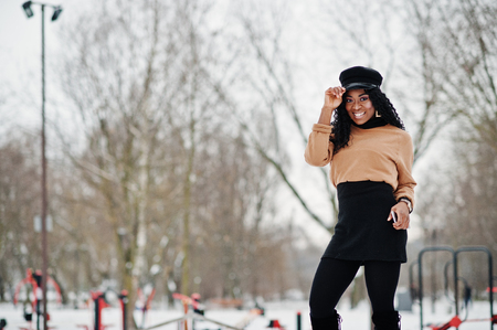 African american woman in black skirt, brown sweater and cap posed at winter day against snowy background, holding phone at hand.