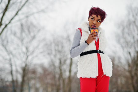 African american woman in red pants and white fur coat jacket posed at winter day against snowy background and holding cup of coffee. Stock Photo