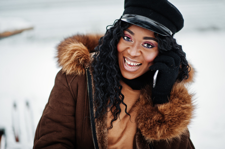 4817c7a1eb9d0 Close up face of african american woman in sheepskin coat and cap posed at  winter day