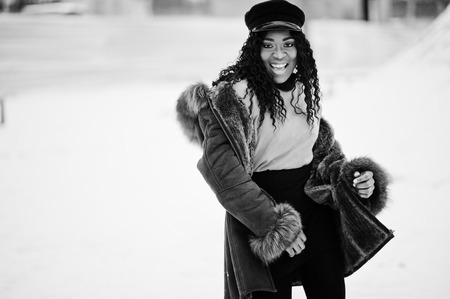 African american woman in sheepskin coat and cap posed at winter day against snowy background.
