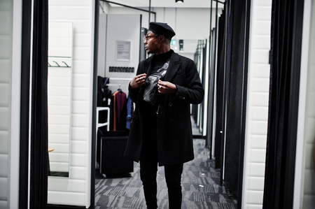 Stylish casual african american man at black beret and overcoat with waist bag at fitting room clothes store, looking on mirror.