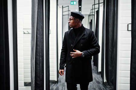 Stylish casual african american man at black beret and overcoat at fitting room clothes store. Stockfoto