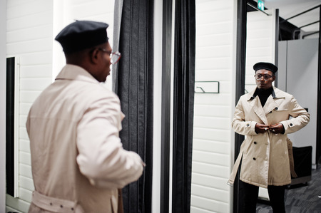 Stylish casual african american man at black beret and white trench raincoat at fitting room clothes store , looking at mirror.