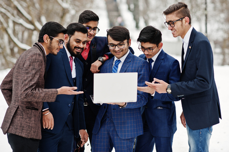 Group of six indian businessman in suits posed outdoor in winter day at Europe, looking on laptop.