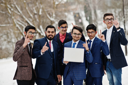 Group of six indian businessman in suits posed outdoor in winter day at Europe, looking on laptop and show fingers up.