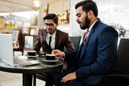 Two indian business man in suits sitting at office on cafe, looking at laptop and drinking coffee.