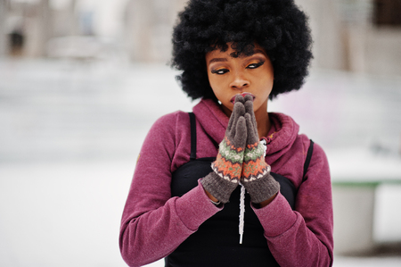 Curly hair african american woman with gloves, hands together like praying, posed at winter day. 免版税图像