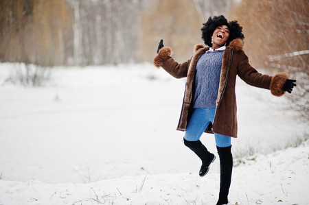 Curly hair african american woman wear on sheepskin coat and gloves posed at winter day, having fun and jump. Stockfoto