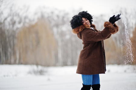 Curly hair african american woman wear on sheepskin coat and gloves posed at winter day throws up snow.