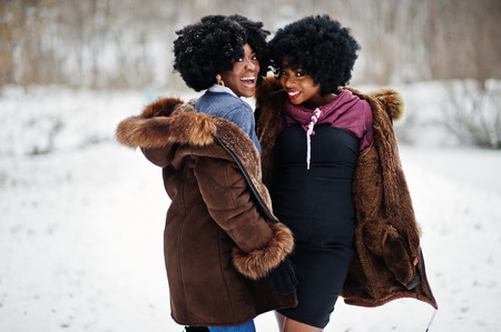 Two curly hair african american woman wear on sheepskin coat and gloves posed at winter day.