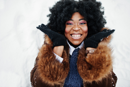 Close up head of curly hair african american woman wear on sheepskin coat and gloves posed at winter day, lies in the snow and laughing.