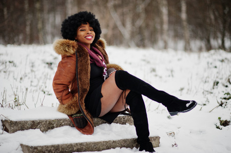 Curly hair african american woman wear on sheepskin coat and gloves posed at winter day.