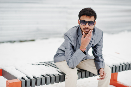 Casual young indian man in silver jacket and sunglasses posed at winter day and sitting on bench. Stock Photo