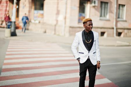 Chic handsome african american man in white suit walking on crosswalk.