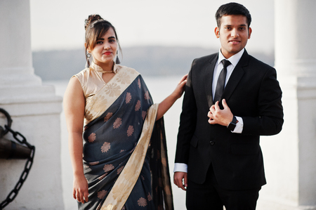 Elegant and fashionable indian friends couple of woman in saree and man in suit posed on the shore of the marina.