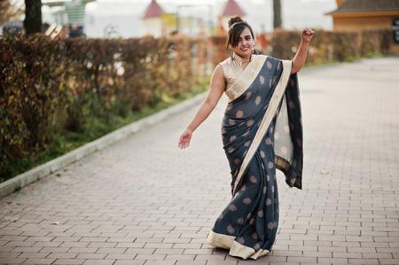 Elegant brunette south asian indian girl in saree dancing outdoor.