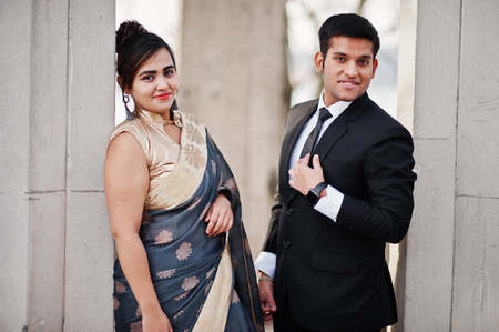 Elegant and fashionable indian friends couple of woman in saree and man in suit posed under arch.