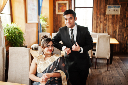 Elegant and fashionable indian friends couple of woman in saree and man in suit posed indoor cafe.