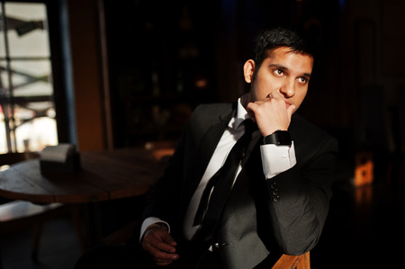 Elegant south asian indian business man in black suit posed indoor cafe in sun shadows. 免版税图像