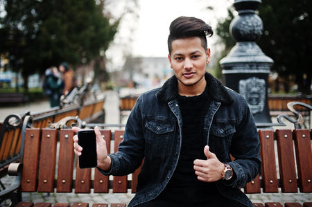 Handsome and fashionable indian man in black jeans jacket posed outdoor, sitting on bench with mobile phone at hand, showing thumb up. Stock fotó