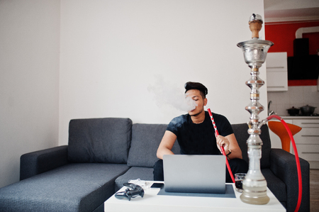 Handsome and fashionable indian man in black sitting at room, smoking hookah and working on laptop.