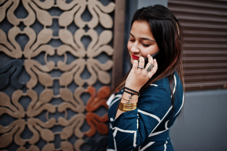 Brunette indian woman in long fashionable dress posed outdoor and speaking at mobile phone.