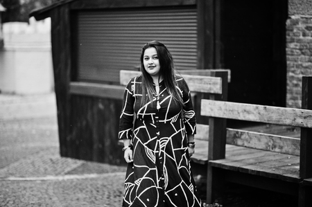 Brunette indian woman in long fashionable dress posed outdoor.