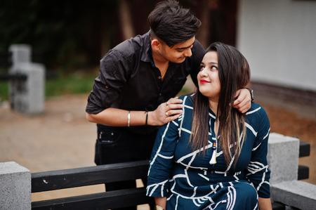 Love story of indian couple posed outdoor, sitting on bench together.