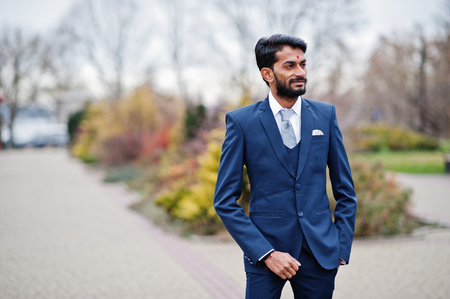 Stylish beard indian man with bindi on forehead, wear on blue suit posed outdoor.