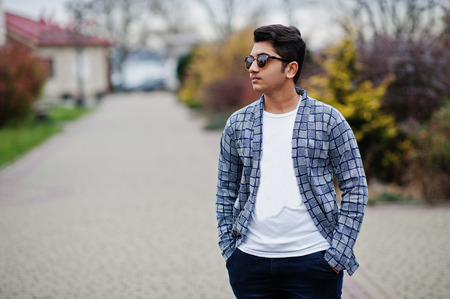 Stylish indian young man at sunglasses wear casual posed outdoor.