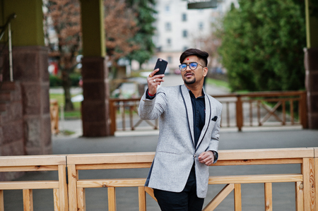 Stylish indian business man with bindi on forehead and glasses, wear on gray suit posed outdoor and making selfie at mobile phone. Imagens