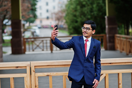 Indian young man at glasses, wear on suit with red tie posed outdoor and making selfie on mobile phone.