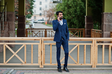 Stylish beard indian business man with bindi on forehead, wear on blue suit posed outdoor and speaking at mobile phone.