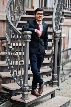Indian young man at glasses, wear on black suit with red tie posed outdoor against iron stairs.