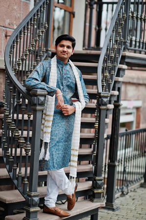 Indian man wear on traditional clothes with white scarf posed outdoor against iron stairs.