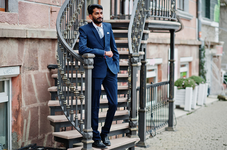 Stylish beard indian man with bindi on forehead, wear on blue suit posed outdoor against iron stairs.