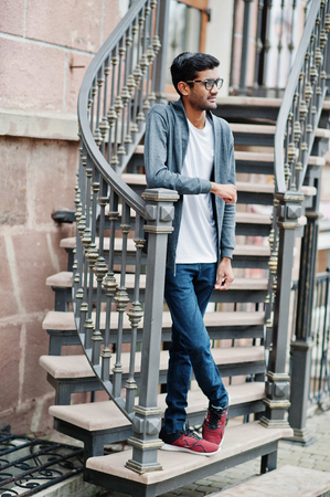 Stylish indian man at glasses wear casual posed outdoor against iron stairs.