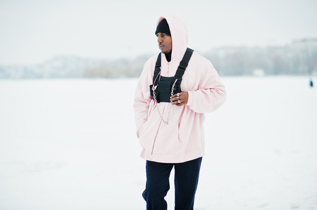 Stylish urban style african american man in pink hoodie posed at frozen lake in winter.