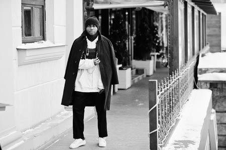 Stylish urban style african american man in black coat and hat, pink hoodie posed at winter day. 免版税图像
